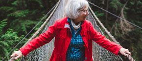 An older woman crosses a rope bridge