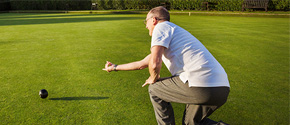 A man rolls a ball on a lawn