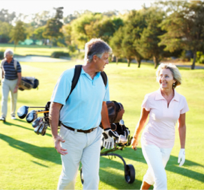 A man and woman walking on a golf course