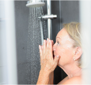 Woman washing her face in the shower
