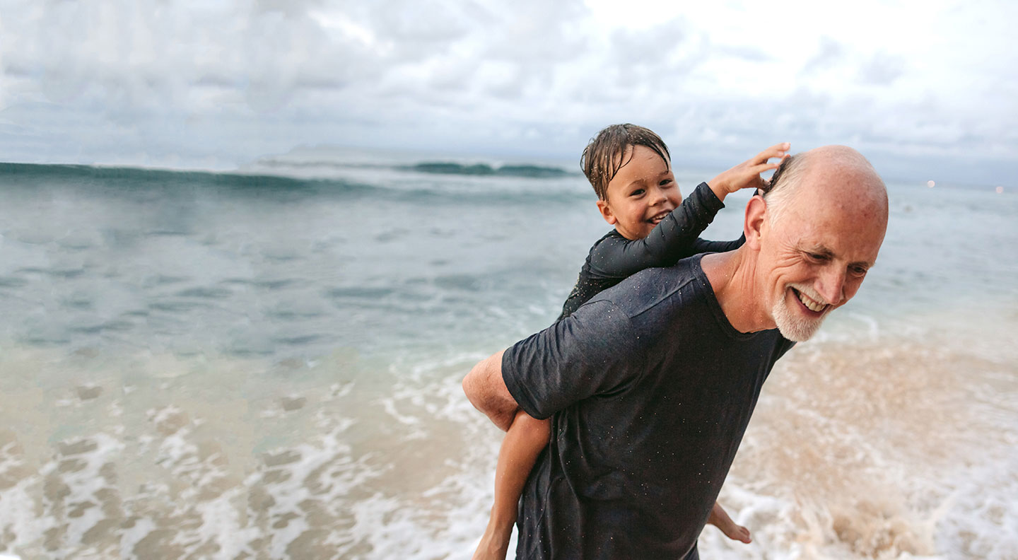 An older man at the beach carrying a young boy piggyback.